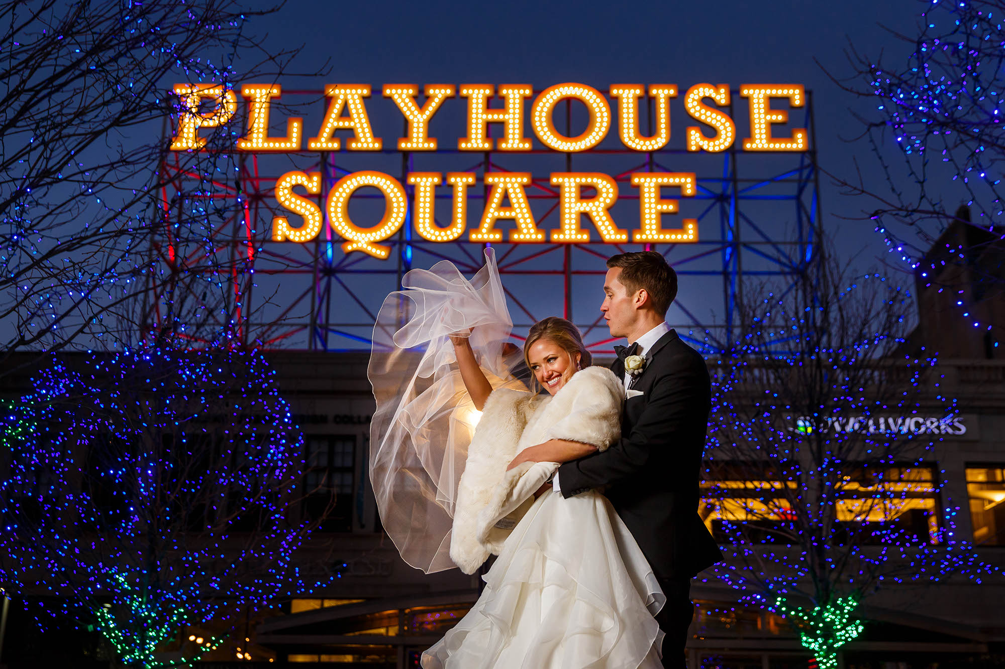 Bride catches her veil before it blows away outside of Playhouse Square in Cleveland.