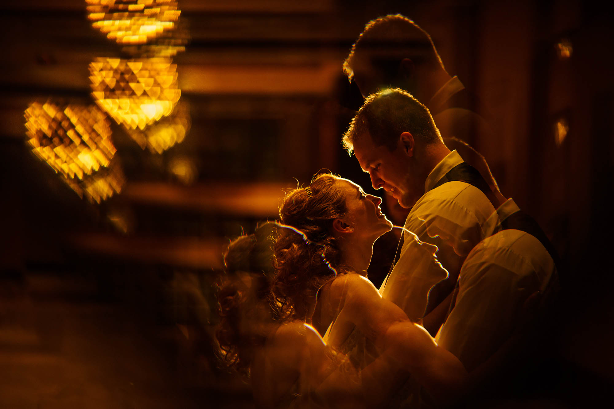 Multiple reflections of the bride and groom shot through a cut glass window at the Bertram Inn in Aurora, Ohio.
